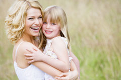 Draußen lächelnde Mutterholdingtochter lizenzfreie stockfotografie