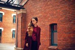 Draußen Lebensstilmodeporträt des Brunettemädchens Tragender stilvoller roter Mantel Gehen zur Stadtstraße Langes gelocktes helle stockbild