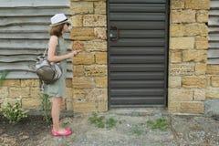Draußen nennt Mädchen die Wechselsprechanlage und steht nahe der Haustür stockfotografie