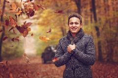 Draußen Porträt des glücklichen jungen Mannes, der im Herbstpark an steht Stockfoto