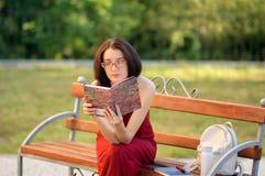 Draußen Porträt des klugen jungen weiblichen Jugendlichen in Eyesglasses mit Buch in den Händen, die auf der Bank in der Stadt si Stockbilder