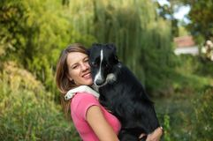 Draußen Porträt des lächelnden schönen Mädchens, das ihren weißen und schwarzen Hund auf Händen während des Sommertages hält Stockfoto