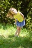 Draußen Porträt des netten blonden Mädchens in der hellen Kleidung, die im Park während Sunny Days aufwirft und die Kamera betrac Lizenzfreie Stockfotografie