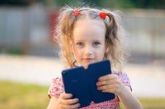 Draußen Porträt des netten Mädchens mit blauen Augen und zwei den Pferdeschwänzen, die Smartphone in den Händen halten und betrac Lizenzfreies Stockfoto
