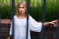 Draußen Porträt der jungen attraktiven Blondine durch Metallstangen Lizenzfreie Stockfotografie