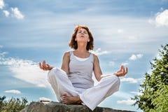 Draußen trainieren für Mitte alterte die Yogafrau, die auf einem Stein sitzt Stockfoto