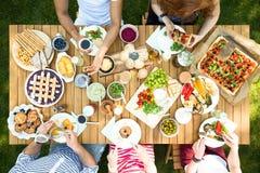 Draufsicht über die Leute, die das Mittagessen am Gartentisch während der Partei essen stockfotos
