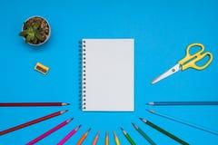 Draufsicht über ein Anmerkungsbuch mit freiem Raum und Schulbedarf Färben Sie Bleistifte, Bleistiftspitzer und Scheren auf einem  Lizenzfreies Stockbild