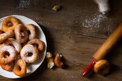 Draufsicht über ein Bündel frische selbst gemachte Schaumgummiringe (Donuts) auf einer weißen Platte, mit Zuckerschüssel, Nudelho Lizenzfreie Stockbilder