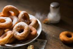 Draufsicht über ein Bündel frische selbst gemachte Schaumgummiringe (Donuts) auf einer weißen Platte, mit Zuckerschüssel, Nudelho Stockfotos