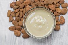 Draufsicht über eine Mandel-Butter in einer Glasschüssel mit Mandeln lizenzfreies stockbild