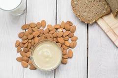 Draufsicht über eine Mandel-Butter in einer Glasschüssel mit Milch und Brot lizenzfreie stockfotos