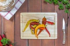 Draufsicht über konservierte in Essig eingelegte Paprika-Pfeffer auf einem hackenden Brett lizenzfreies stockbild