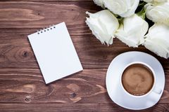 Draufsicht über Notizbuch, Kaffeetasse und Blumenstrauß von Rosen auf Holzoberfläche Romantische Sammlung Tapeten Stockfoto