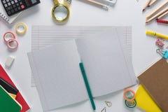 Draufsicht über Schulbedarf als Taschenrechner, Machthaber, Bänder, Büroklammern, Notizbücher und anderes Material gelegt in eine lizenzfreies stockbild