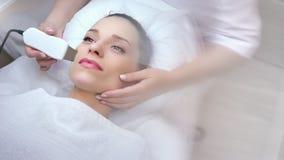 Draufsicht Berufscosmetologisthände, die Gesichtsverfahren mit moderner Ausrüstung machen stock footage