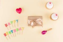 Draufsicht der alles- Gute zum Geburtstagbeschriftung, des Umschlags mit Band und der köstlichen kleinen Kuchen auf Rosa Lizenzfreies Stockbild