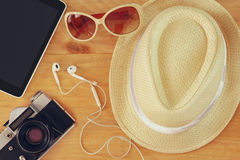 Draufsicht der alten Kamera der stilvollen Hutfrauen-Sonnenbrille und des Tablettengerätes über Holztisch vaction und Reisekonzep Lizenzfreie Stockfotografie