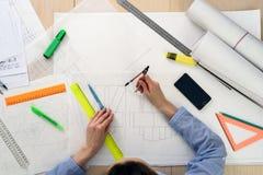 Draufsicht der Architekt ` s Frau bei der Arbeit über das Design des Gebäudes, auf dem Tisch Papier, Machthaber, Bleistifte, Komp Lizenzfreie Stockfotos