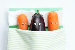 Draufsicht der Aubergine liegend mit zwei Karotten im Bett lizenzfreie stockbilder