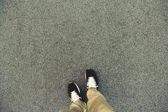 Draufsicht der Beine und der Schuhe, die auf der Asphaltstraße stehen Mak Lizenzfreies Stockbild