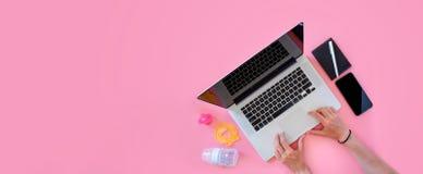 Draufsicht der berufstätigen Mutter flatlay von den Arbeitsplatzbabyeinzelteilen und -laptop mit Telefon Stockfotografie