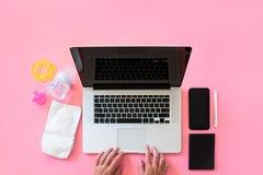 Draufsicht der berufstätigen Mutter flatlay von den Arbeitsplatzbabyeinzelteilen und -laptop mit Telefon Lizenzfreie Stockbilder