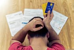Draufsicht der betonten jungen asiatischen Mannsorge über das Beschaffen des Kapitals, um Kreditkarteschuld zu zahlen stockfoto