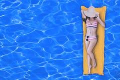 Draufsicht der dünnen jungen Frau im Bikini, der auf der gelben Luftmatraze im Swimmingpool mit Kopienraum sich entspannt stockfotos