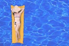 Draufsicht der dünnen jungen Frau im Bikini, der auf der gelben Luftmatraze im Swimmingpool sich entspannt stockfoto