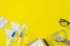 Draufsicht der Doktorschreibtischtabelle mit Stethoskop, Spritzen, Impfeinspritzungen, Tablette und Notizbuch mit Stift Beschneid stockfoto