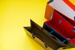 Draufsicht der Einkaufspapiertüten über gelben Hintergrund mit Kopienraum stockfotografie