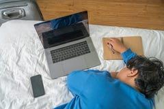Draufsicht der erschöpften Asiatin, die auf Bett schläft lizenzfreie stockfotografie