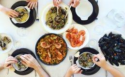 Draufsicht der Familie Paella und Meeresfrüchte um eine weiße Tabelle vom hohen Blickwinkel essend stockfotografie