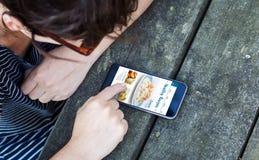 Draufsicht der Frau, die Smartphone über Holztisch mit Gesundheit verwendet lizenzfreie stockfotografie