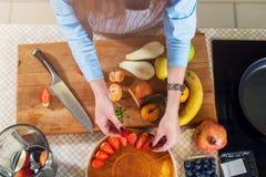 Draufsicht der Frau eine Kuchenschicht mit Erdbeere verzierend Hausfrau, die Fruchttorte kocht stockfotografie