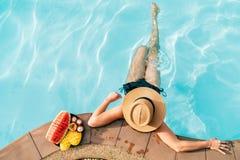 Draufsicht der Frau im Strohhut, der auf Swimmingpoolseite nahe Platte der Kamera der tropischen Früchte sitzt stockbild