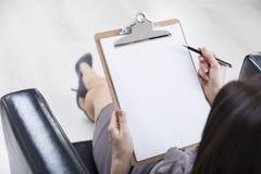 Draufsicht der Frauenhand mit Klemmbrett Stockfotografie