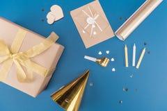 Draufsicht der Geschenkbox, der Kerzen, des Geburtstagshutes und des Umschlags lokalisiert auf Blau Stockfotos