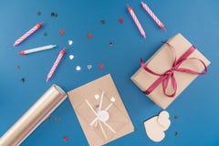 Draufsicht der Geschenkbox, der Kerzen und des Umschlags lokalisiert auf Blau Lizenzfreies Stockfoto
