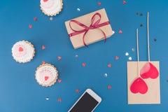 Draufsicht der Geschenkbox, des Smartphone, der Kuchen und des Umschlags auf Blau Lizenzfreie Stockbilder