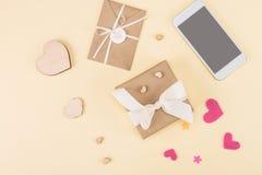 Draufsicht der Geschenkbox, des Smartphone und des Umschlags lokalisiert auf Beige Stockbilder