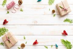 Draufsicht der Geschenkbox, der Kiefernkegel, des roten Sternes und der Glocke auf einem hölzernen weißen Hintergrund lizenzfreies stockfoto