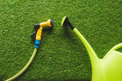 Draufsicht der Gießkanne und der Schlauchleitung auf Gras, minimalistic Konzeption stockbilder
