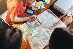 Draufsicht der Gruppe Studentinnen, welche die Karte sitzt am Schreibtisch studieren stockbilder
