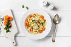 Draufsicht der Hühnersuppe mit Teigwaren, Karotte und Petersilie auf Weiß Stockfoto