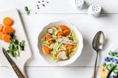 Draufsicht der Hühnersuppe mit Teigwaren, Karotte und Petersilie auf Weiß Stockfotografie