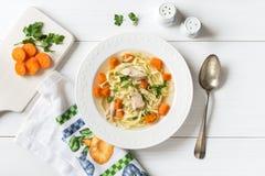 Draufsicht der Hühnersuppe mit Teigwaren, Karotte und Petersilie auf Weiß Lizenzfreie Stockfotos