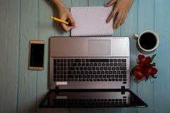 Draufsicht der Hand der Frau schreiben etwas auf leeres Papier nahe Laptop und Telefon Stockbild
