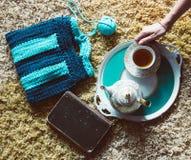 Draufsicht der handgemachten gestrickten Handtasche, des Buches, der Teekanne und der Schale stockfotos